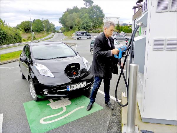 圖為一名挪威車主正在幫電動車充電。(路透檔案照)