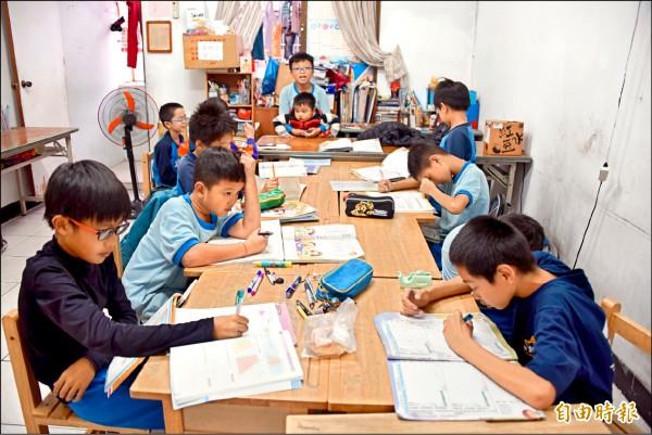 孩子們自己坐好寫作業,準備上輔導課。(記者葉永騫攝)