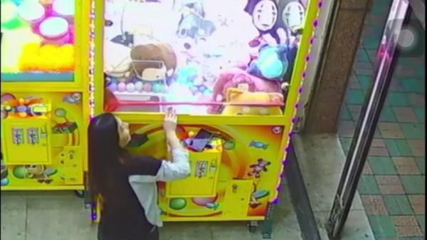 蔡女先以掃把伸進機台內,撥弄娃娃撈近取物口。(記者許國楨翻攝)