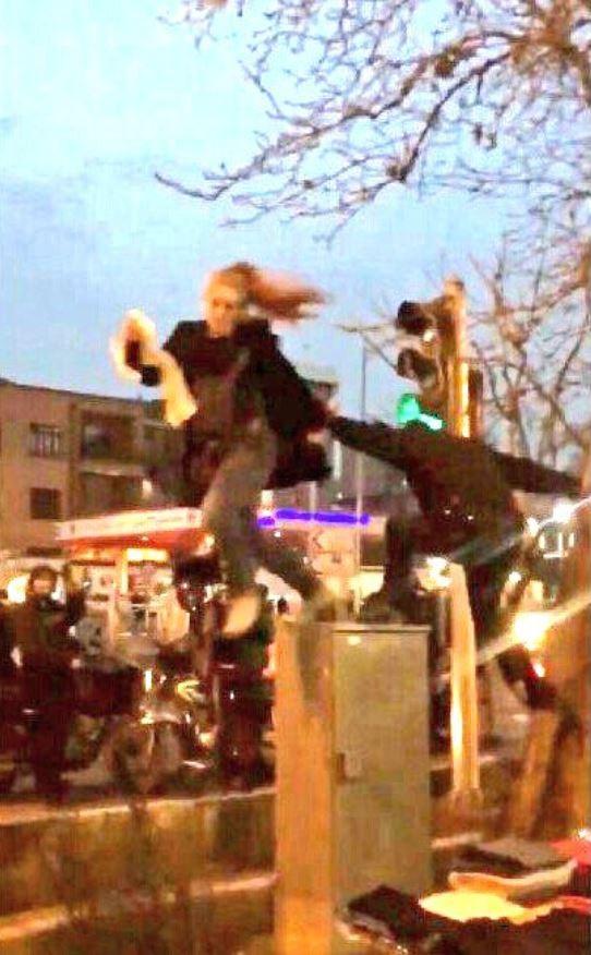 伊朗一名女子上街頭,站在配電箱抗議女性外出時必須戴頭巾的規定,竟遭一名警察強硬推下,引發現場群眾嘩然。(圖擷自推特)