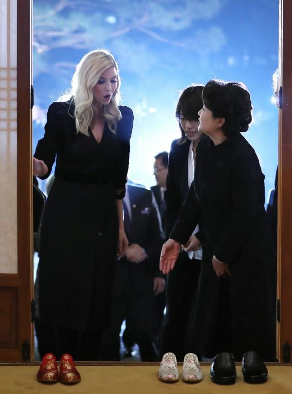 美國總統川普女兒、第一千金伊凡卡(Ivanka Trump,左)出訪南韓,韓國第一夫人金正淑(右)特別為她準備大紅喜氣繡花拖鞋,讓她在晚宴穿上,似乎正向伊凡卡說明韓國入室脫鞋的習慣。(歐新社)