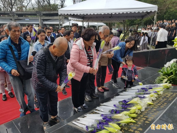 台南各界今在新營228紀念公園舉行追思音樂會,受難者家屬在紀念碑前獻花。(記者王涵平攝)