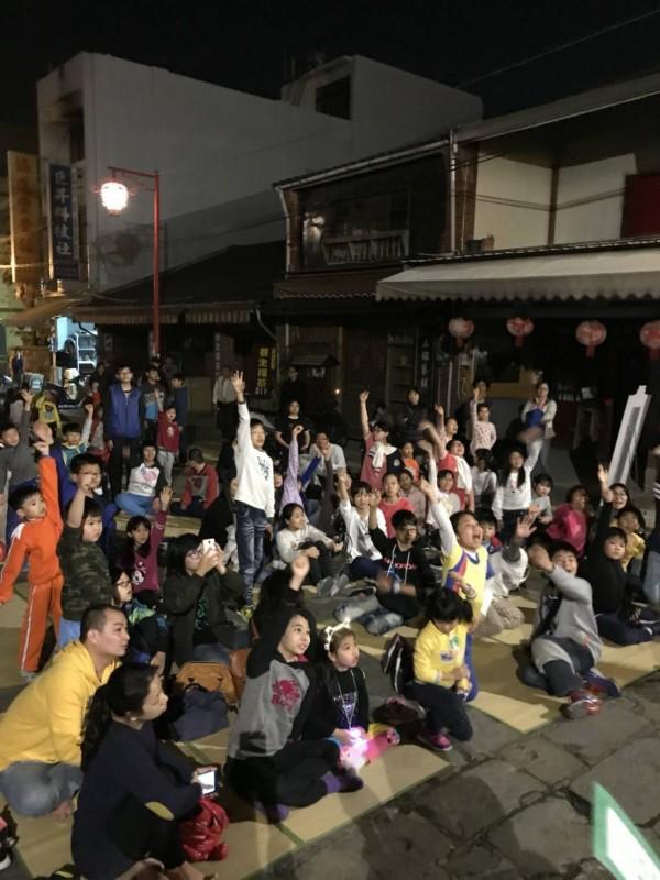 在當地商家熱心贊助下,民眾持油笐火遊行之後,坐在慈天宮廟前廣場參與猜燈謎活動。(彭煥章提供)