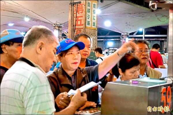 劉乃禎一站上拍賣台氣勢十足,神情專注,隨時掌握承銷人的手勢、語意。(記者蕭婷方攝)