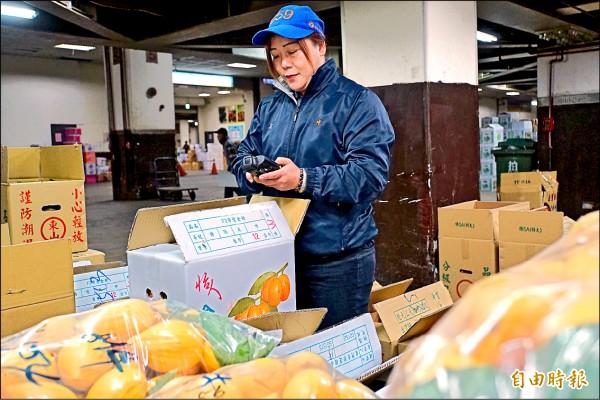 劉乃禎每日到市場上的例行公事就是先為理好貨的水果裁價,等待凌晨四點開始拍賣喊價(記者蕭婷方攝)