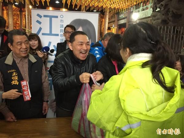 新北市前副市長侯友宜笑著和民眾聊天賣菜,展現親民態度。(記者邱書昱攝)