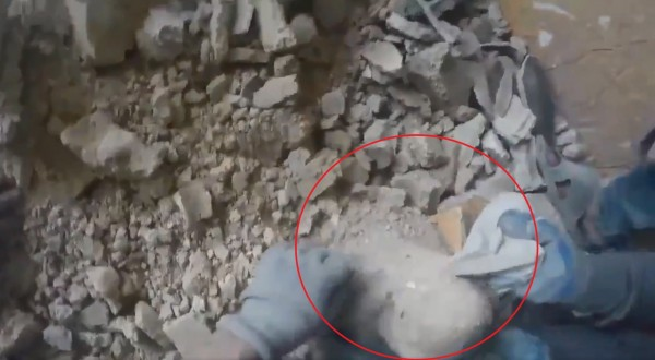 敘利亞東古塔一位女嬰遭轟炸後的建築碎石掩埋,竟奇蹟被救援人員活著「從石堆中挖出」。圖為包著女嬰身體的布料。(圖片擷取自@ismailSCD推特影片)