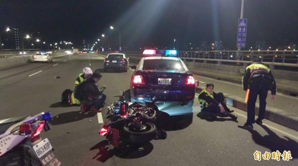 1輛紅牌大型重機今晚行經浮洲橋往板橋方向,衝撞板橋警分局路檢點,造成3警及肇事騎士4人受傷,其中1警頭部外傷、1人左小腿骨折,警方正釐清肇事責任。(記者吳仁捷攝)