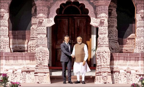 印度總理莫迪(右)十一日在新德里歡迎來訪的法國總統馬克宏,參加國際太陽能聯盟成立大會。(路透)