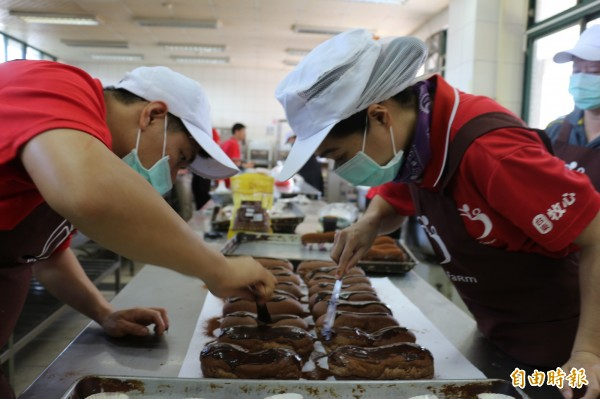 牧心烘焙庇護工場的學員為髒髒包塗上濃厚的巧克力醬。(記者王秀亭攝)