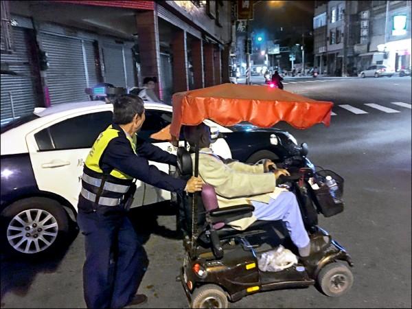 蔡太雄(左)推老翁及電動車回派出所。(記者洪定宏翻攝)