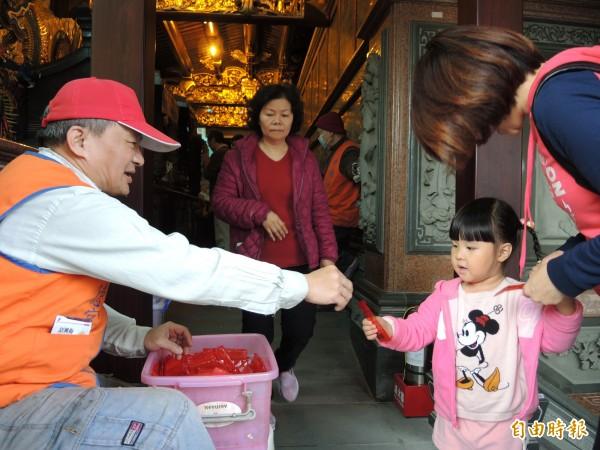 廟方發給每位信眾2元的小紅包,可帶回家當錢母。(記者翁聿煌攝)