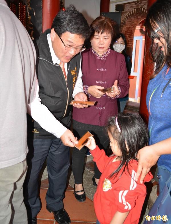 彰化市長邱建富(左)發放由文昌帝君加持過的「追分成功書籤」給信眾。(記者湯世名攝)