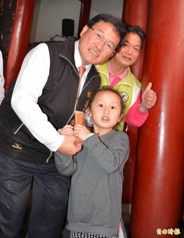 彰化市長邱建富(左)發放由文昌帝君加持過的「追分成功書籤」給信眾,連小朋友也搶著要。(記者湯世名攝)