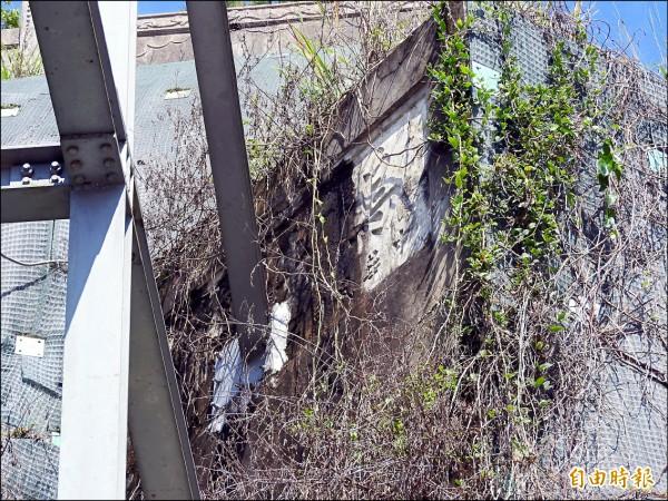 南投縣埔里鎮公所在愛蘭橋旁設置大型電子看板,其中的支撐鋼樑就直接打進舊烏牛欄橋石碑,遭質疑破壞珍貴文物。(記者佟振國攝)