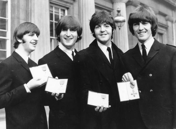 「披頭四」成員於1965年10月26日在白金漢宮前,展示了英國女王伊麗莎白二世所頒予的大英帝國勳章。(美聯社)