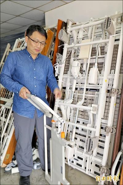 新北輔具中心主任楊忠一展示民眾捐出的病床,其中的扶手可折疊調整兼當輔具。(記者何玉華攝)