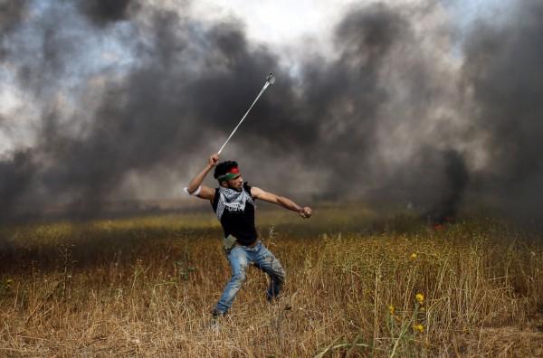 巴勒斯坦抗議群眾朝以色列軍方丟擲石塊。(路透)
