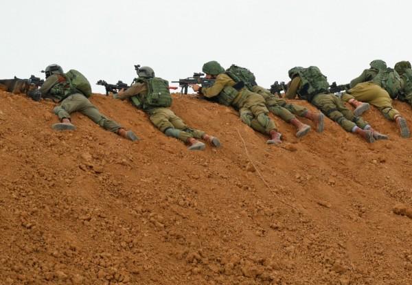 以色列軍方人員趴在土丘上,對逼近的巴勒斯坦抗議群眾開火。(法新社)