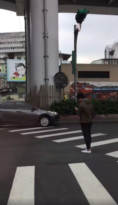 台北市市民大道三段與安東街口,有個男子竟在等紅燈時,站在馬路上且低頭滑手機。(圖擷取自爆廢公社)