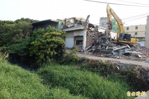 鹿港溪河道兩岸未取得合法建照的用戶,已有人自行僱工拆除。(記者劉曉欣攝)