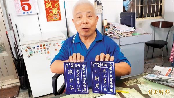 陳樹菊的弟弟從姊姊的攤位找出兩塊藍色牌子,是五十五年前承租的登記牌。(記者黃明堂攝)
