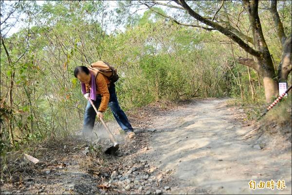 林惠遠爬山帶著鋤頭,發現排水道阻塞,就會清除土石維持暢通。(記者陳建志攝)