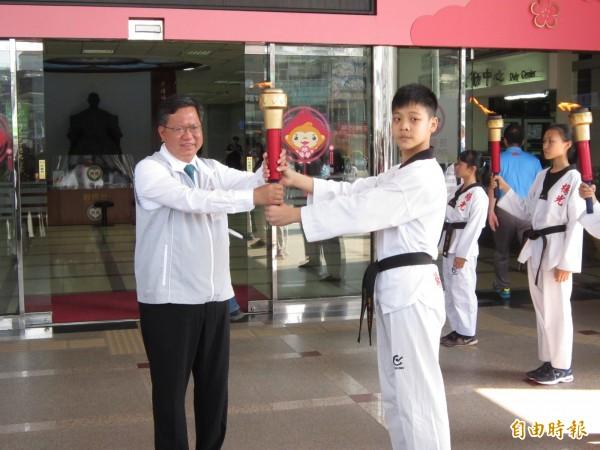 亞洲少年跆拳道品勢銅牌選手莊安寶將聖火傳遞給市長鄭文燦。(記者謝武雄攝)
