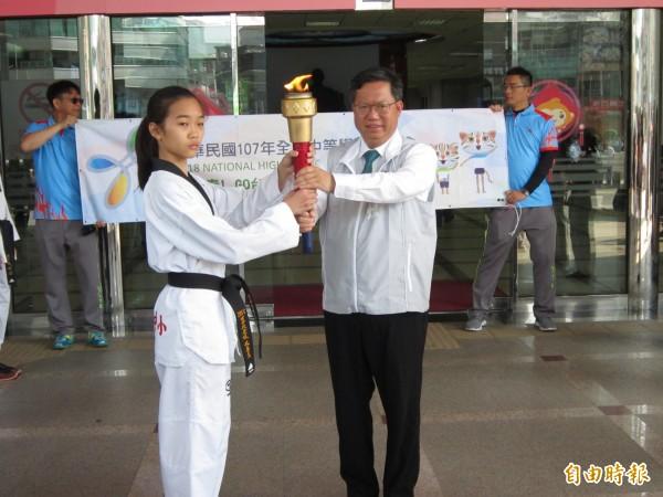 市長鄭文燦隨後將聖火傳遞給去年全中運跆拳金牌選手楊尋真,象徵傳承。(記者謝武雄攝)