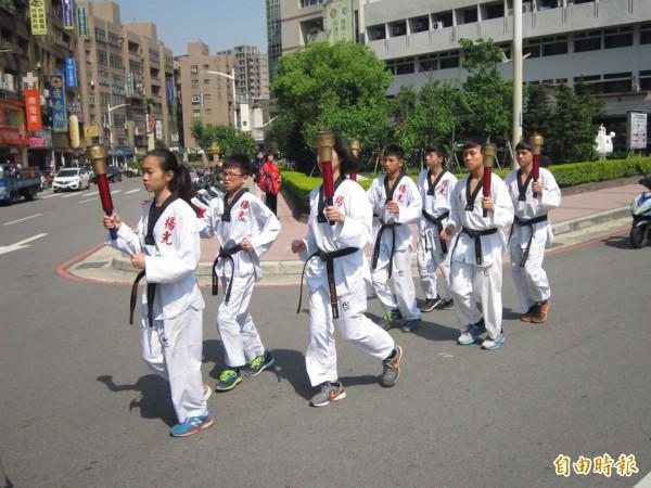 聖火隊伍在去年全中運跆拳金牌選手楊尋真帶領下離開桃園。(記者謝武雄攝)