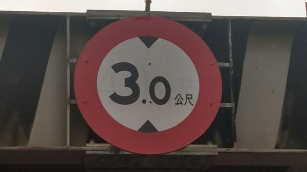 這個限高3公尺的警示標誌,市府3單位推諉設置,導致正義街、康樂街地下道填平工程延宕。(記者張瑞楨翻攝)