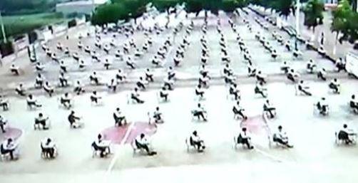 中國一間國中將考場搬到戶外,不少應考學生直喊超熱。(圖截自鳳凰新聞)