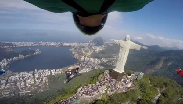 極限運動員身著飛鼠裝在空中滑翔,與巨大耶穌像擦身而過。(圖擷自YouTube)