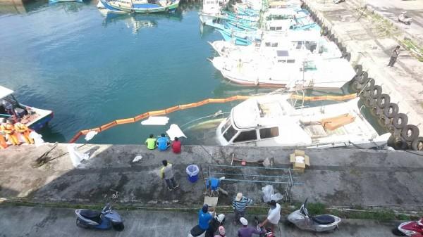 遊艇燕魚一號半沉港區,海巡人員緊急以攔油索等避免油汙造成港區汙染。(記者王秀亭翻攝)