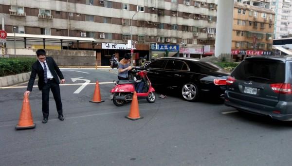 台北市市民大道微風廣場大門前,發生機車撞上千萬名車賓利的事故,而這輛賓利是微風廣場的公務車,保全立刻拿出交通錐保留事故現場。(記者陳恩惠翻攝)