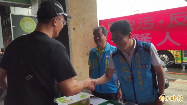 國民黨基隆市長提名人謝立功(右)在基隆城隍廟前擺攤,希望民眾一同參與連署反對設立深澳電廠。(記者林欣漢攝)
