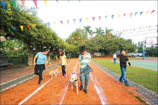 讓訓練中的導盲犬進到校園,孩子們可學習到如何陪伴動物。(記者李惠洲/攝影)