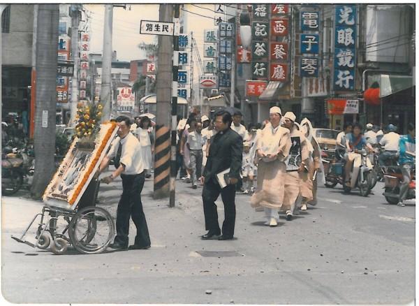 1985年,男子「阿嵐」推著黨外人士王燈岸的遺照繞行全彰化市區,讓王家人至今懷念不已。(圖:王鏡玲提供)
