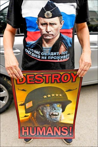 身穿印有俄羅斯總統普廷肖像的塞爾維亞抗議者,十五日在首都貝爾格勒舉著反北約組織海報,抗議美國、英國和法國聯軍空襲敘利亞。(法新社)