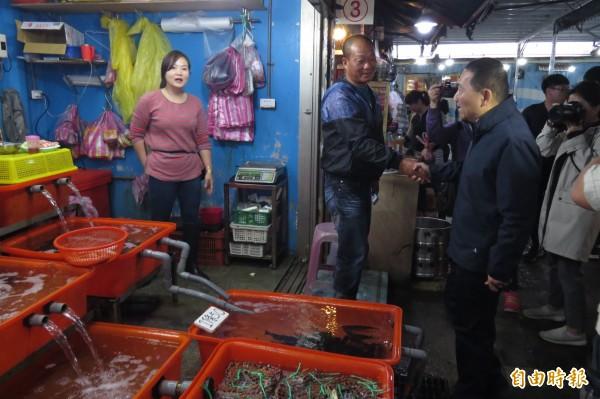 國民黨新北市長提名人侯友宜今天(17日)走訪萬里區龜吼漁港漁夫市集,受到攤商歡迎。(記者俞肇福攝)