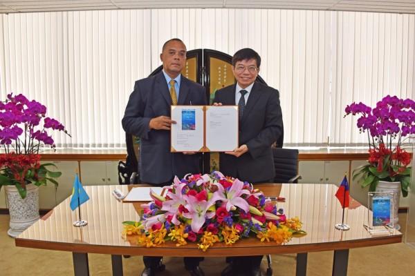 中華郵政董事長王國材(右),金宇帛琉郵政總長Timothy R. Sinsak(左)簽署郵票授權契約書。(圖:中華郵政提供)