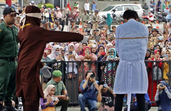 亞齊特區今天公開執行鞭刑,吸引上千名遊客聚集,還拍照、錄影。(歐新社)