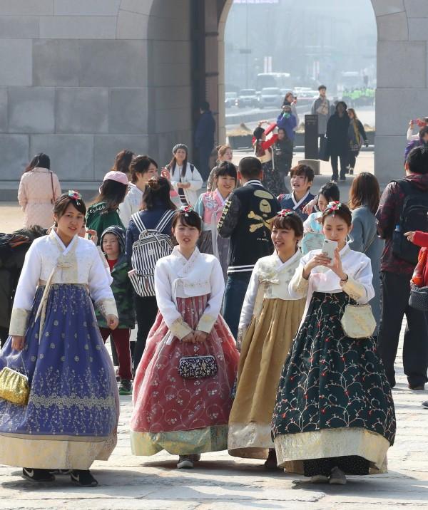 南韓中客大量減少,但推動旅遊多元化後,今年3月前往南韓的外國觀光客,比去年同期增加10.7%!圖為南韓景福宮的遊客穿著傳統韓服。(歐新社)