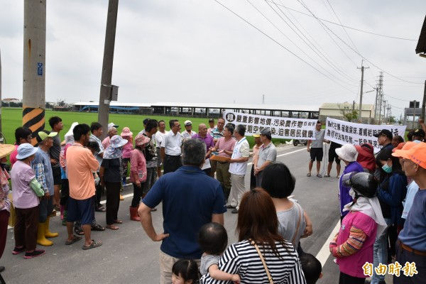 反對與雞舍為鄰、拒絕雞屎味污染,大埤鄉嘉興村民齊聚養雞場外拉白布條抗議。(記者黃淑莉攝)
