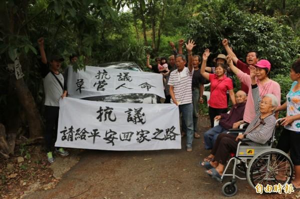 居民舉白布條抗議,希望法院撤回縮路的命令。(記者鄭名翔攝)