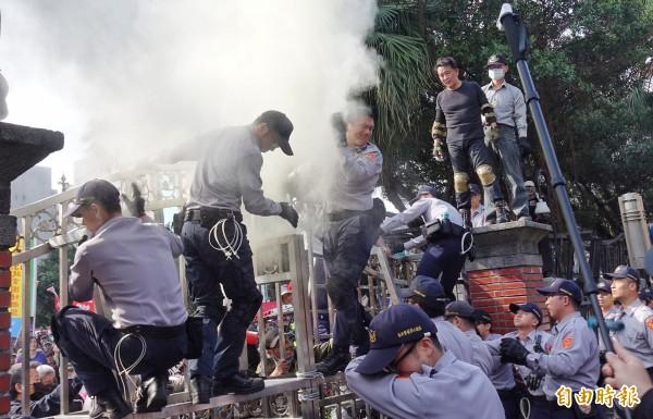反年改團體八百壯士強攻立法院大門,還疑似對值勤員警投擲煙霧彈。(記者劉信德攝)