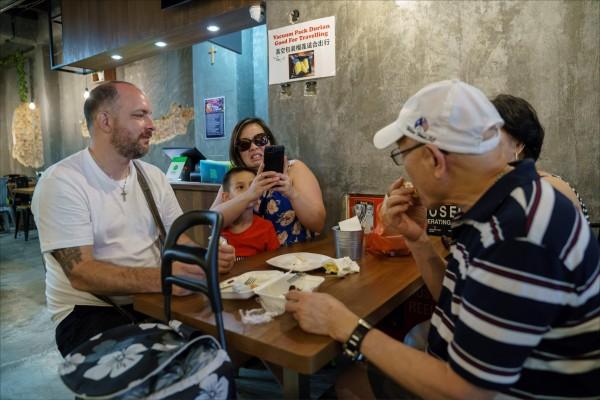新加坡的貓山王榴槤咖啡店裡,遊客正在品嚐榴槤料理,一旁的家人卻露出詭異表情。  (法新社檔案照)