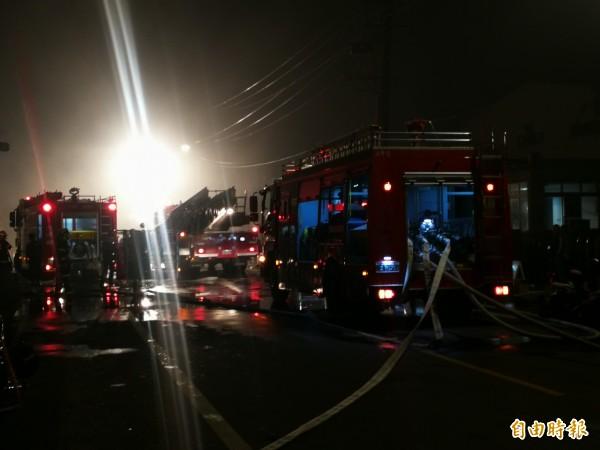 火場內溫度極高,仍有4名消防員遭崩塌物壓住受困,現場出動雲梯車及水車灌救降溫。(記者許倬勛攝)