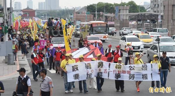 遊行勞工高舉「反過勞」、「拚公投」、「要加薪」、「爭勞權」等標語。(記者方賓照攝)