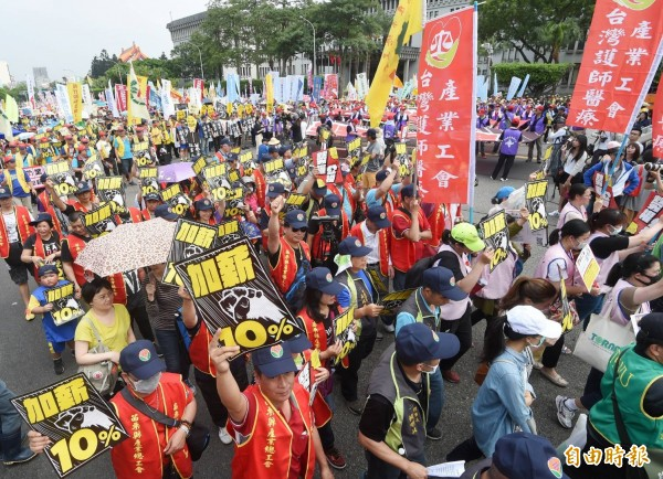 遊行勞工高舉標語牌,爭取每年加薪10%。(記者方賓照攝)
